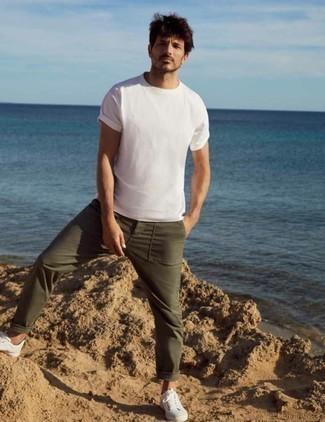 Herren Outfits 2020: Kombinieren Sie ein weißes T-Shirt mit einem Rundhalsausschnitt mit einer olivgrünen Chinohose, um einen lockeren, aber dennoch stylischen Look zu erhalten. Weiße Segeltuch niedrige Sneakers sind eine kluge Wahl, um dieses Outfit zu vervollständigen.