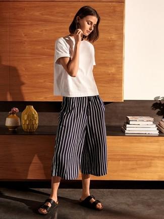 Schwarze flache Sandalen aus Leder kombinieren – 201 Damen Outfits: Ein weißes T-Shirt mit einem Rundhalsausschnitt und ein schwarzer und weißer vertikal gestreifter Hosenrock sind absolut Freizeit-Essentials und können mit einer Vielzahl von Kleidungsstücken kombiniert werden, um ein müheloses, entspanntes Outfit zu erreichen. Schwarze flache Sandalen aus Leder sind eine großartige Wahl, um dieses Outfit zu vervollständigen.
