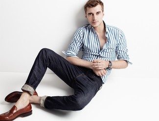 Wie kombinieren: weißes und blaues vertikal gestreiftes Langarmhemd, schwarze Jeans, braune Leder Slipper