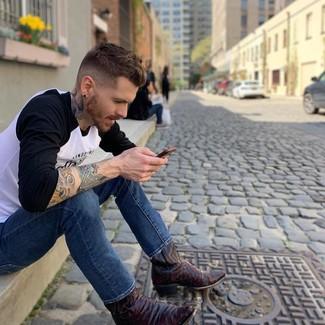 Wie kombinieren: weißes und schwarzes bedrucktes Langarmshirt, blaue Jeans, dunkelrote Cowboystiefel aus Leder