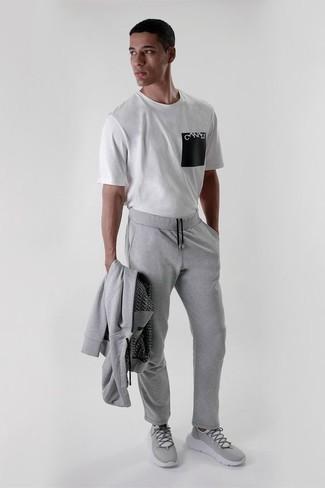 Trainingsanzug kombinieren: trends 2020: Für ein bequemes Couch-Outfit, kombinieren Sie einen Trainingsanzug mit einem weißen und schwarzen bedruckten T-Shirt mit einem Rundhalsausschnitt. Graue Sportschuhe sind eine kluge Wahl, um dieses Outfit zu vervollständigen.