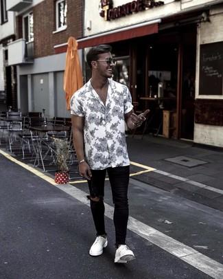 Wie kombinieren: weißes und schwarzes Kurzarmhemd mit Blumenmuster, schwarze enge Jeans mit Destroyed-Effekten, weiße Leder Derby Schuhe