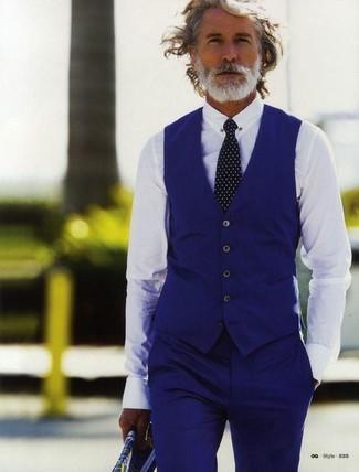Aiden Shaw trägt blaue Weste, weißes Businesshemd, blaue Anzughose, schwarze und weiße gepunktete Krawatte