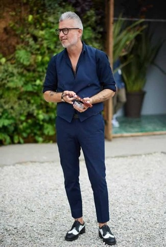 Wie kombinieren: dunkelblaue Weste, dunkelblaues Businesshemd, dunkelblaue Chinohose, schwarze und weiße Leder Brogues