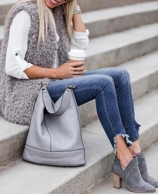 Wie kombinieren: graue Pelzweste, weißes Businesshemd, blaue enge Jeans, graue Wildleder Stiefeletten