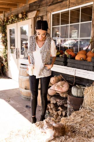 Wie kombinieren: graue Pelzweste mit Reliefmuster, weißer Kurzarmpullover, schwarze enge Hose aus Leder, schwarze Leder Stiefeletten