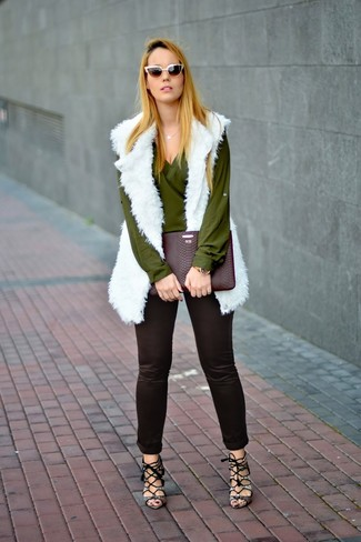 Wie kombinieren: weiße Pelzweste, olivgrüne Langarmbluse, schwarze enge Hose, graue Leder Sandaletten mit Schlangenmuster
