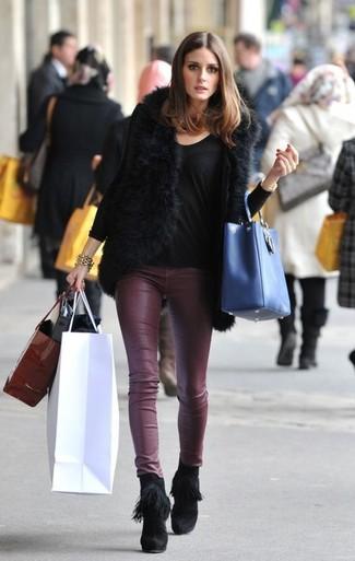 Olivia Palermo trägt schwarze Pelzweste, schwarzes Langarmshirt, dunkelrote enge Hose aus Leder, schwarze Fransen Wildleder Stiefeletten