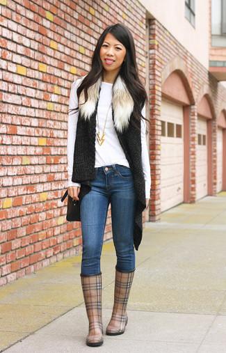 Wie kombinieren: schwarze Strick Pelzweste, weißes Langarmshirt, blaue enge Jeans, braune Gummistiefel mit Schottenmuster