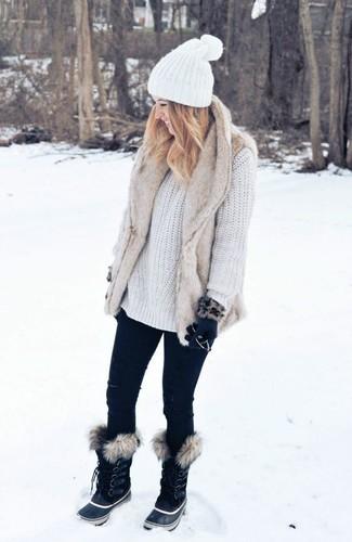Wie kombinieren: hellbeige Pelzweste, weißer Strick Oversize Pullover, schwarze enge Jeans, schwarze Winterschuhe