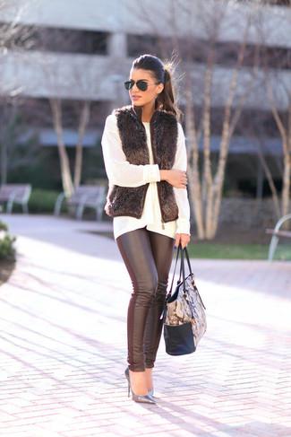 Wie kombinieren: schwarze Pelzweste, weißer Strick Oversize Pullover, schwarze Lederleggings, silberne Leder Pumps