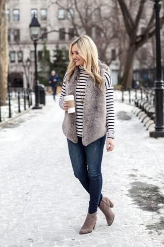 Wie kombinieren: graue Pelzweste, weißer und schwarzer horizontal gestreifter Rollkragenpullover, dunkelblaue enge Jeans, graue Wildleder Stiefeletten