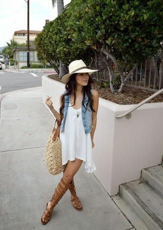 Wie kombinieren: hellblaue Jeansweste, weißes schwingendes Kleid, braune hohe Römersandalen aus Leder, hellbeige Shopper Tasche aus Häkel