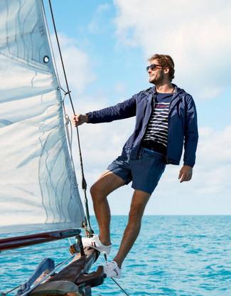 Wie kombinieren: dunkelblaue Windjacke, dunkelblauer und weißer horizontal gestreifter Pullover mit einem Rundhalsausschnitt, dunkelblaue Badeshorts, weiße Segeltuch niedrige Sneakers