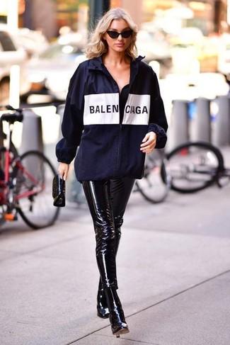 Wie kombinieren: dunkelblaue bedruckte Windjacke, schwarze enge Hose aus Leder, schwarze Leder Stiefeletten, schwarze Leder Clutch