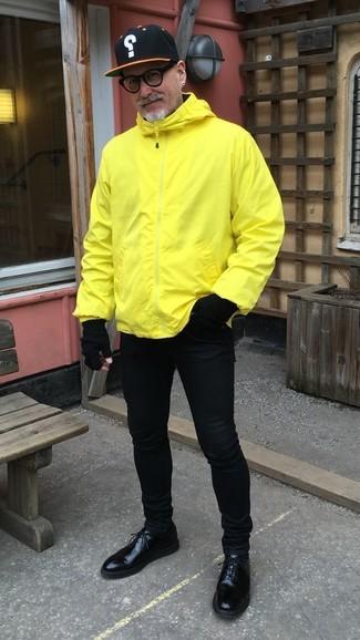 Wie kombinieren: gelbe Windjacke, schwarze enge Jeans, schwarze Leder Derby Schuhe, schwarze bedruckte Baseballkappe