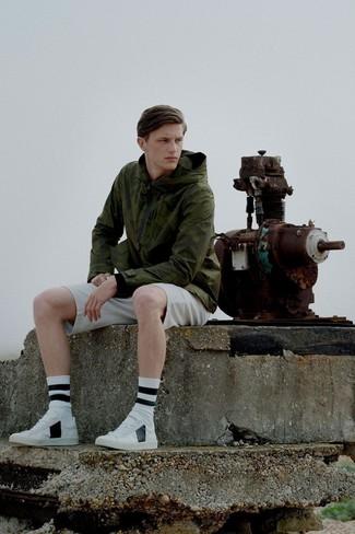 Wie kombinieren: olivgrüne Windjacke, hellbeige Shorts, weiße Leder niedrige Sneakers, weiße und schwarze horizontal gestreifte Socke