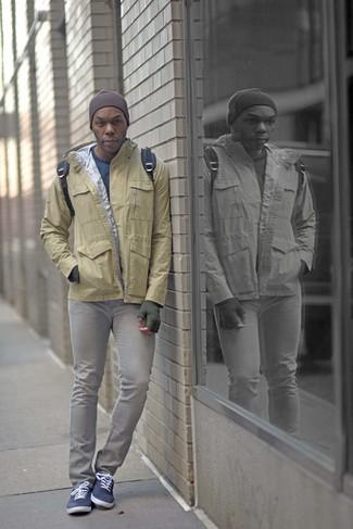 Wie kombinieren: beige Windjacke, blauer Pullover mit einem Rundhalsausschnitt, graue enge Jeans, dunkelblaue Segeltuch niedrige Sneakers