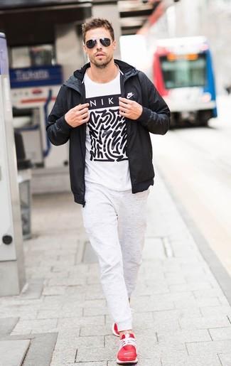 Wie kombinieren: schwarze Windjacke, weißes und schwarzes bedrucktes T-Shirt mit einem Rundhalsausschnitt, weiße Jogginghose, rote Sportschuhe