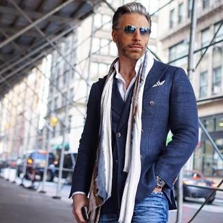Wie kombinieren: dunkelblaues Zweireiher-Sakko aus Baumwolle, weißes Businesshemd, blaue Jeans, hellbeige Schal