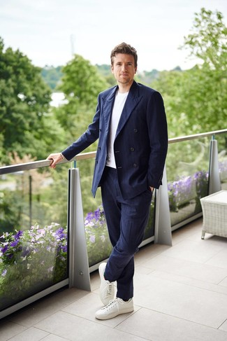Wie kombinieren: dunkelblaues vertikal gestreiftes Zweireiher-Sakko, weißes T-Shirt mit einem Rundhalsausschnitt, dunkelblaue vertikal gestreifte Anzughose, weiße Leder niedrige Sneakers