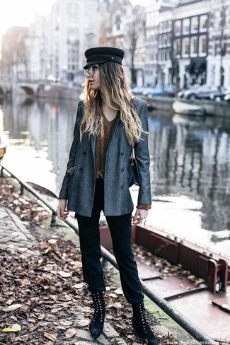 Wie kombinieren: graues Zweireiher-Sakko, goldener Pullover mit einem V-Ausschnitt, schwarze enge Hose, schwarze flache Stiefel mit einer Schnürung aus Wildleder