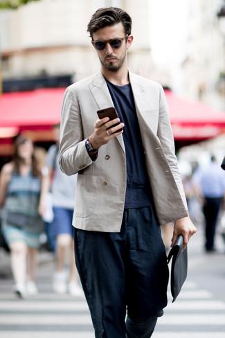 Wie kombinieren: hellbeige Leinen Zweireiher-Sakko, dunkelblaues T-Shirt mit einem Rundhalsausschnitt, dunkelblaue Leinen Chinohose, schwarze Leder Clutch Handtasche