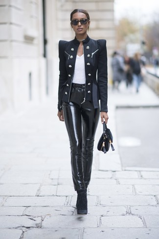 schwarzes Zweireiher-Sakko, weißes T-Shirt mit einem Rundhalsausschnitt, schwarze enge Hose aus Leder, schwarze Samt Stiefeletten für Damen