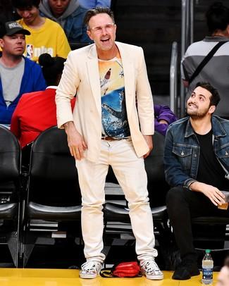 Wie kombinieren: hellbeige Zweireiher-Sakko, mehrfarbiges bedrucktes T-Shirt mit einem Rundhalsausschnitt, hellbeige Jeans, weiße bedruckte Segeltuch niedrige Sneakers