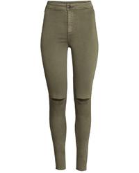 olivgrüne enge Jeans mit Destroyed-Effekten