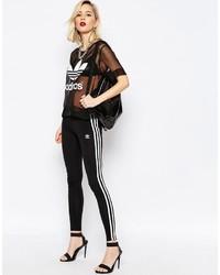 schwarze und weiße vertikal gestreifte Leggings von adidas