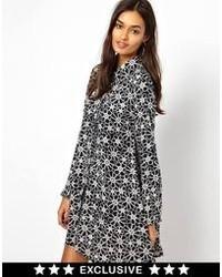 schwarzes und weißes schwingendes Kleid mit Blumenmuster